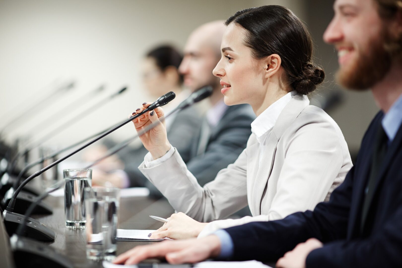 woman speaking into microphone at panel discussion